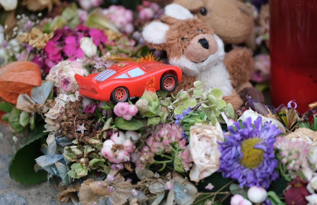A toy car lies among flowers and candles left by mourners at the site of a pedestrian accident