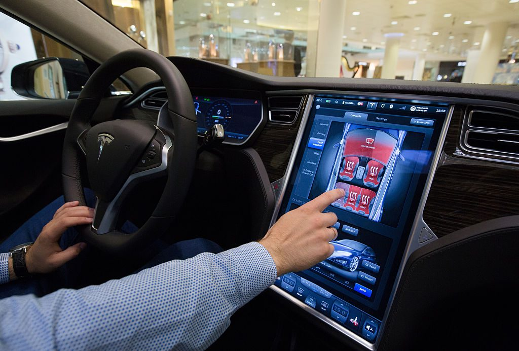 Man sitting in a Tesla using the infotainment screen.