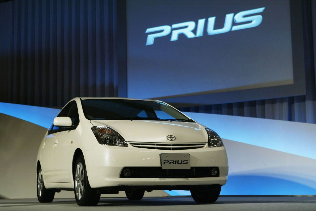 A white Toyota Prius on display at an auto show.