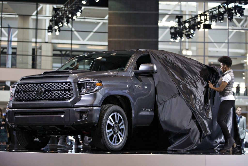 A Toyota Tundra pickup truck being unveiled at an auto show.