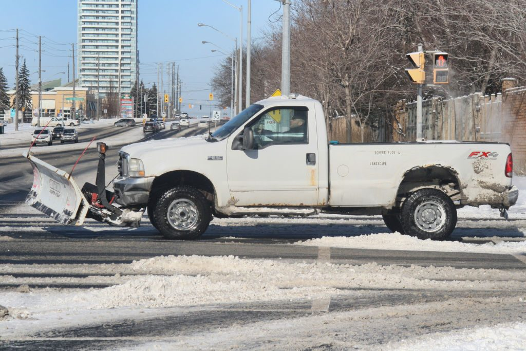 A white pickup truck with a snowplow attached.