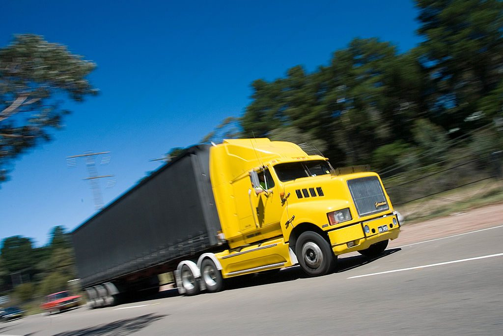 A yellow freight truck speeds down an empty road