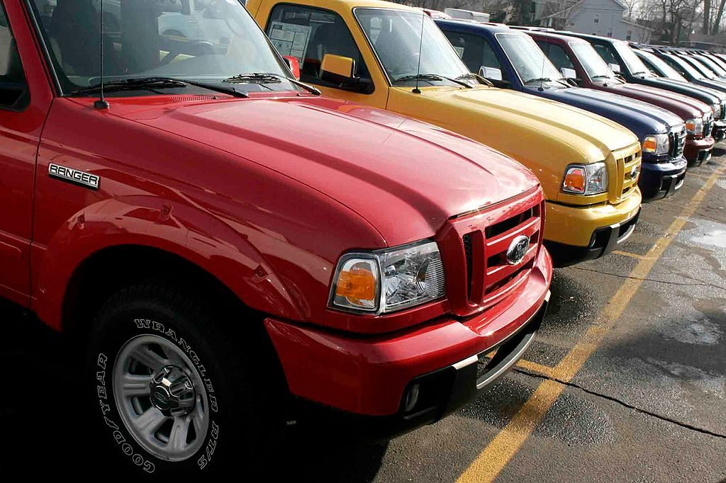 A line of used Ford pickup trucks at a dealership.