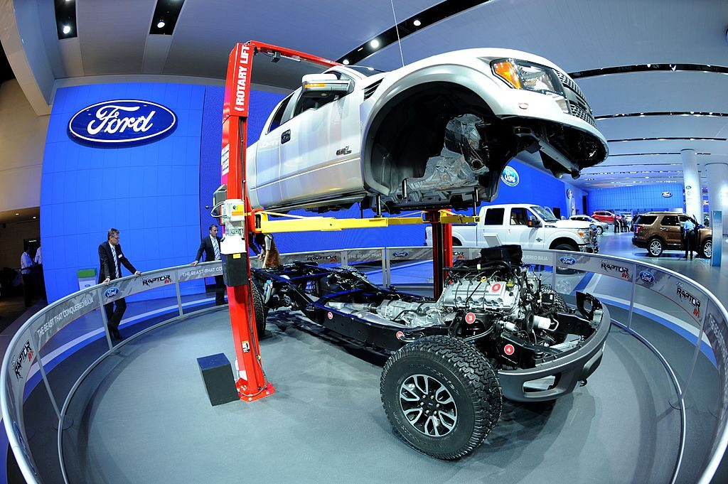 The body of a 2002 Ford F-150 Raptor truck is lifted off its chassis