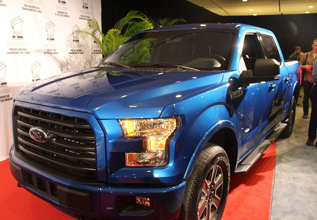 A blue 2015 Ford F-150 on display at an auto show.
