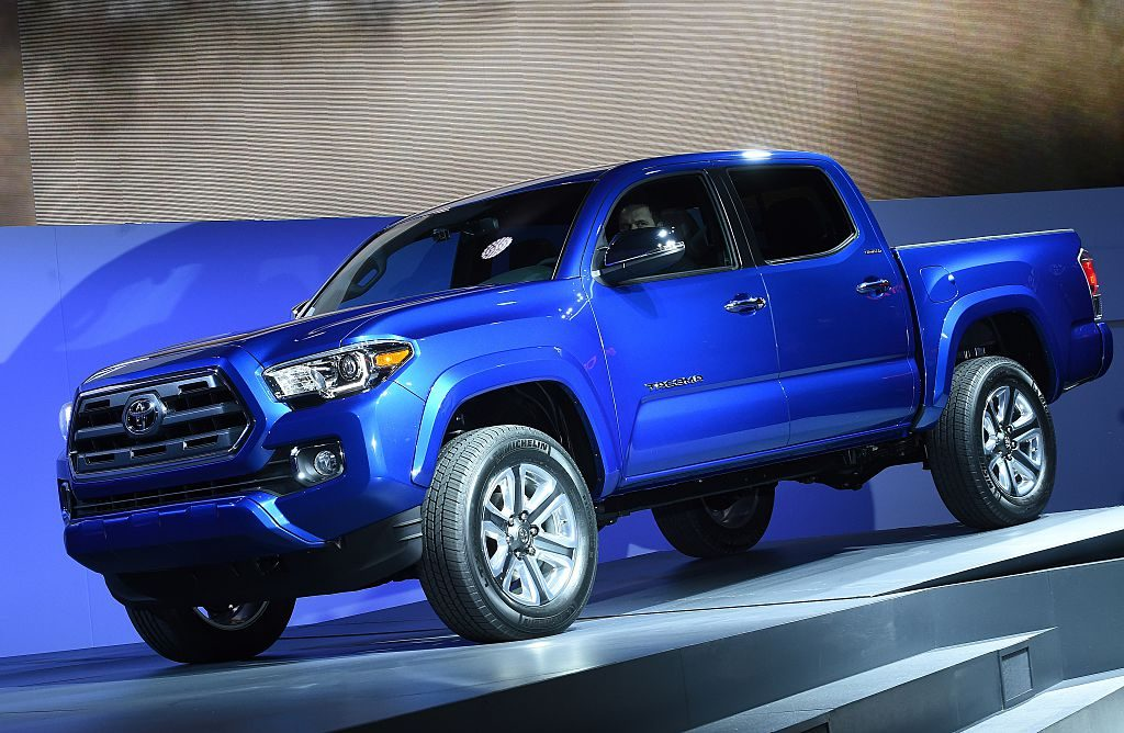 A blue Toyota Tacoma being unveiled at an auto show.