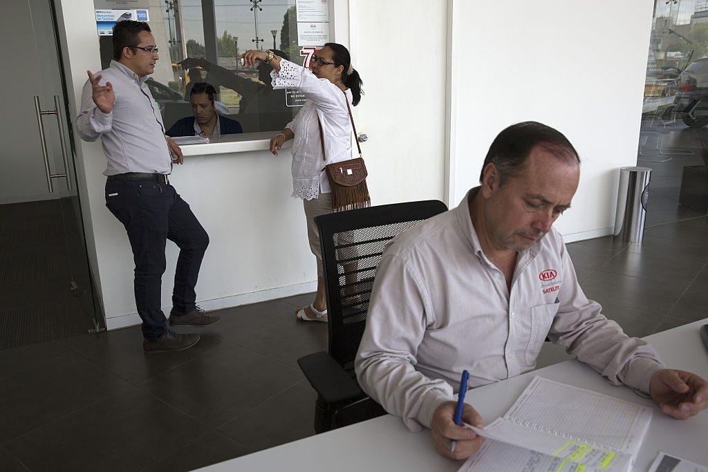 A car dealership salesman works on a sale