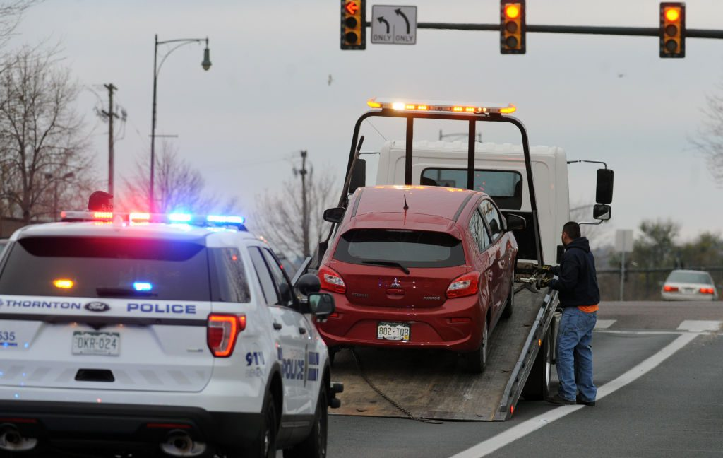A red Mitsubishi is towed in Denve