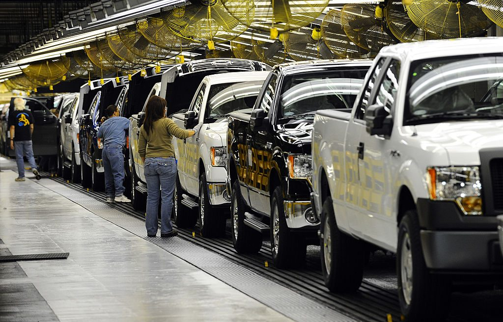 A pickup truck assembly line with different colored trucks being produced.