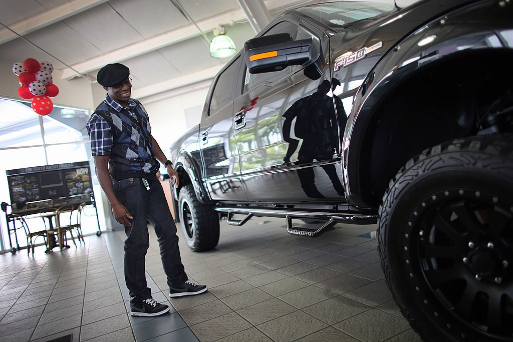 A man looks at a F-150 pickup on the showroom floor at a Ford AutoNation car dealership