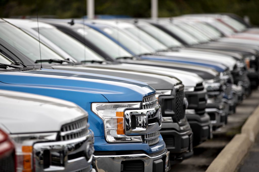 Ford F-150 trucks on display at a car dealership.