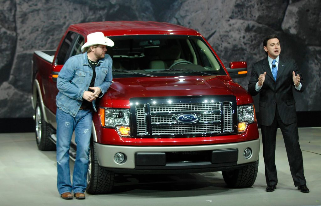 Two people showing off a Ford F-150 at an auto show.