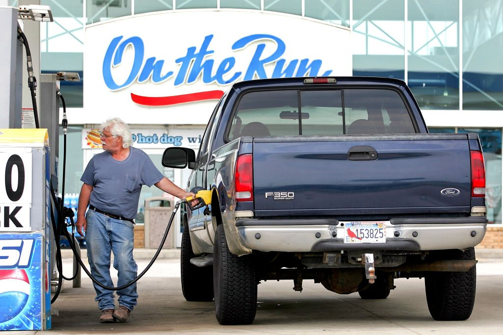 A Ford F-350 heavy-duty truck at a gas station.
