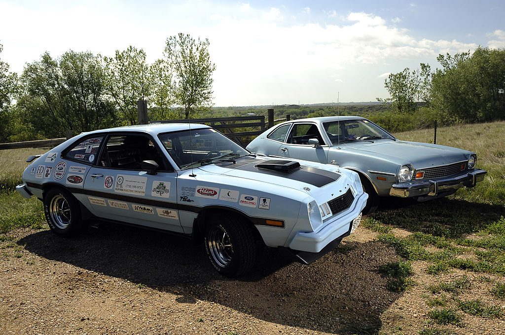 A customized light blue Ford Pinto next to a stock light blue Ford Pinto