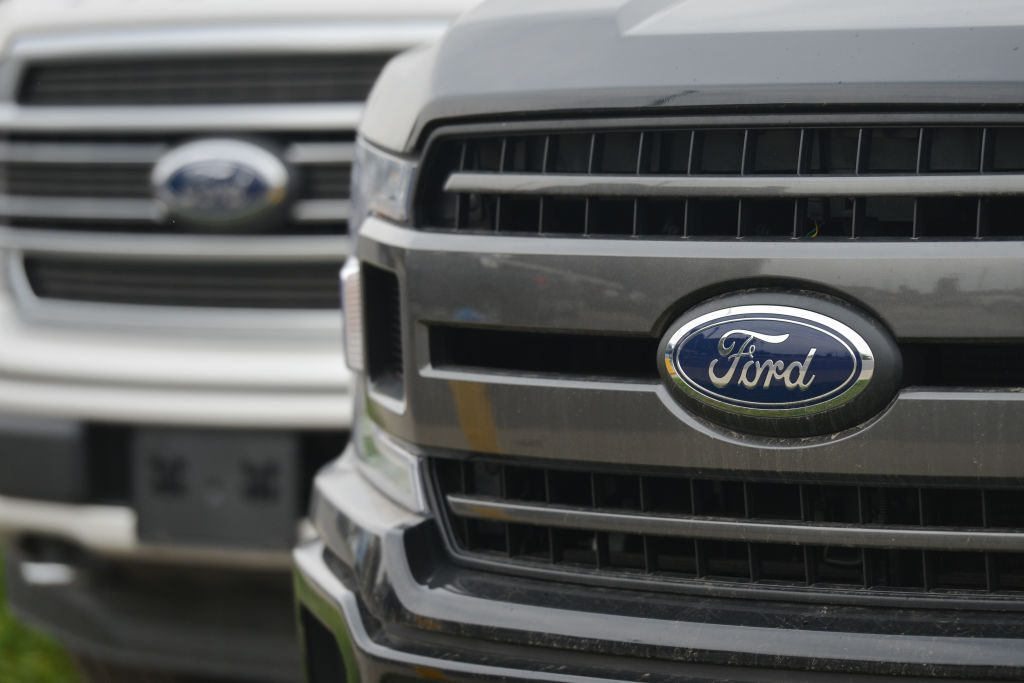 Two Ford trucks on display at an dealership.