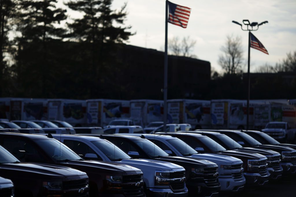 American flags fly near GM Chevrolet pickup trucks displayed for sale at a car dealership