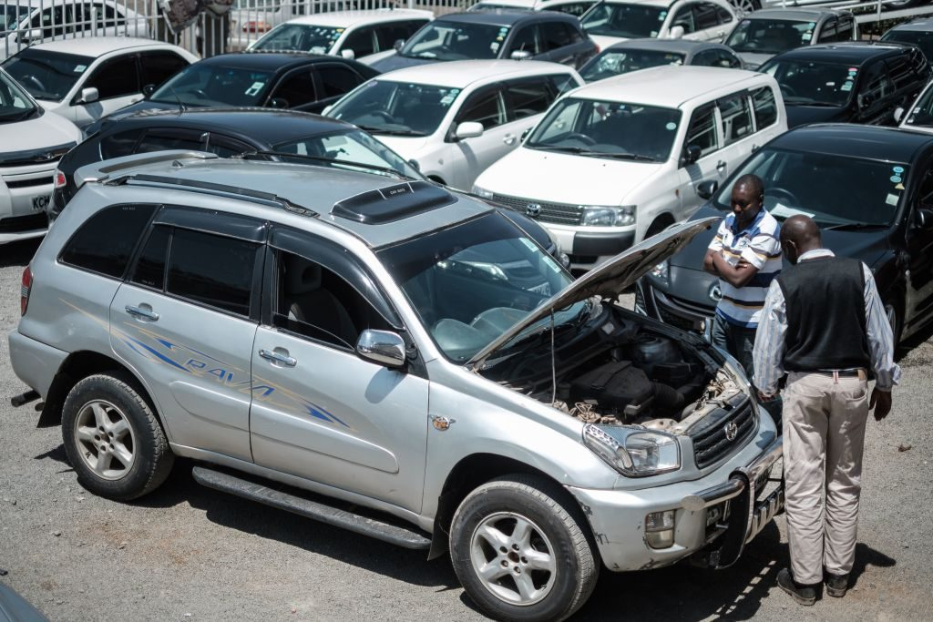 Customers check cars at a used car shop in Nairobi on October 4, 2017. AFP PHOTO / YASUYOSHI CHIBA (Photo credit should read YASUYOSHI CHIBA/AFP via Getty Images)