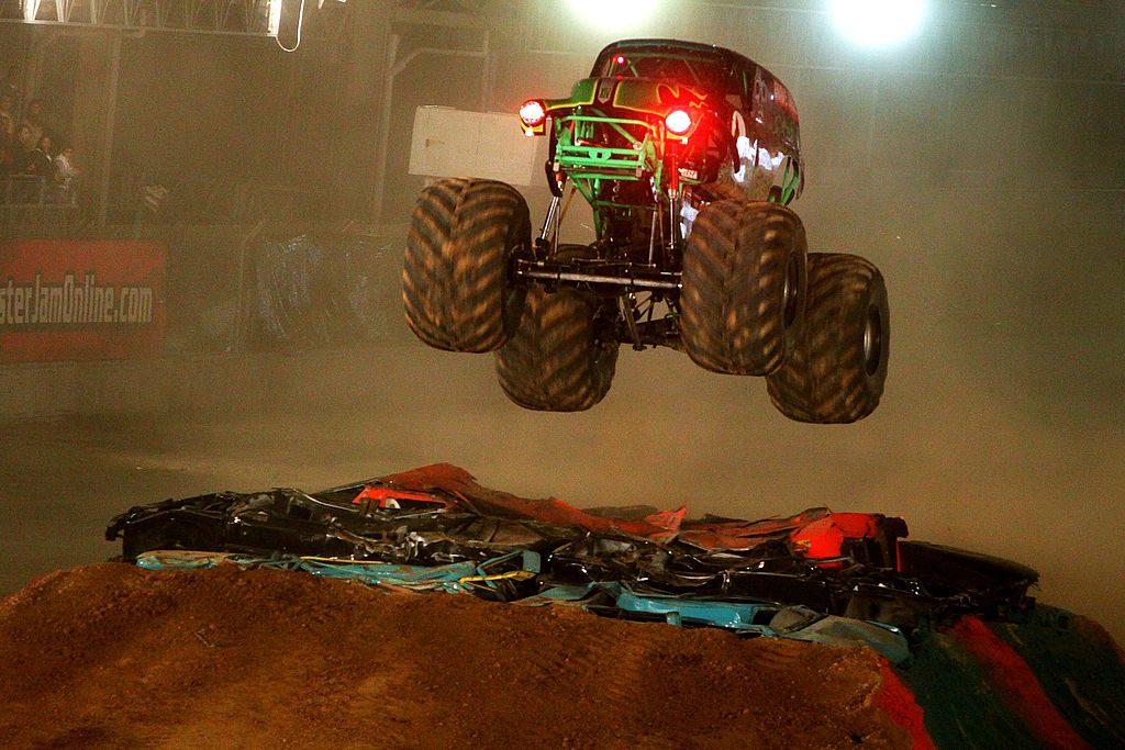 A monster truck launches off of a jump.