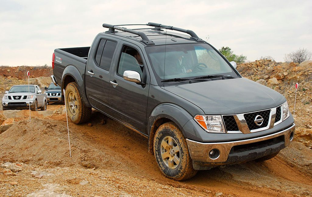 A Nissan Frontier climbing over a dirt hill.