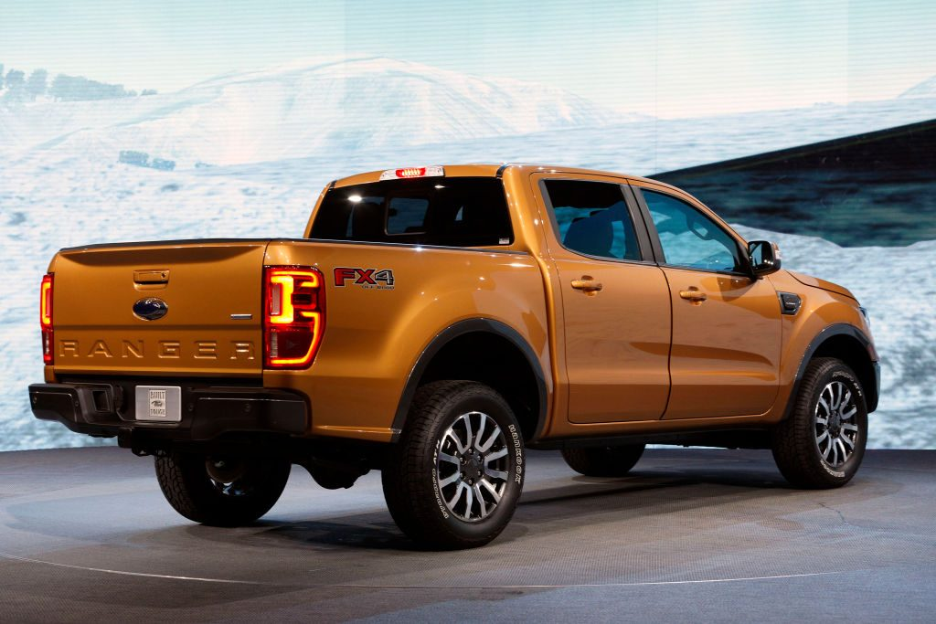 A Ford Ranger in a shiny orange color on display at an auto show.