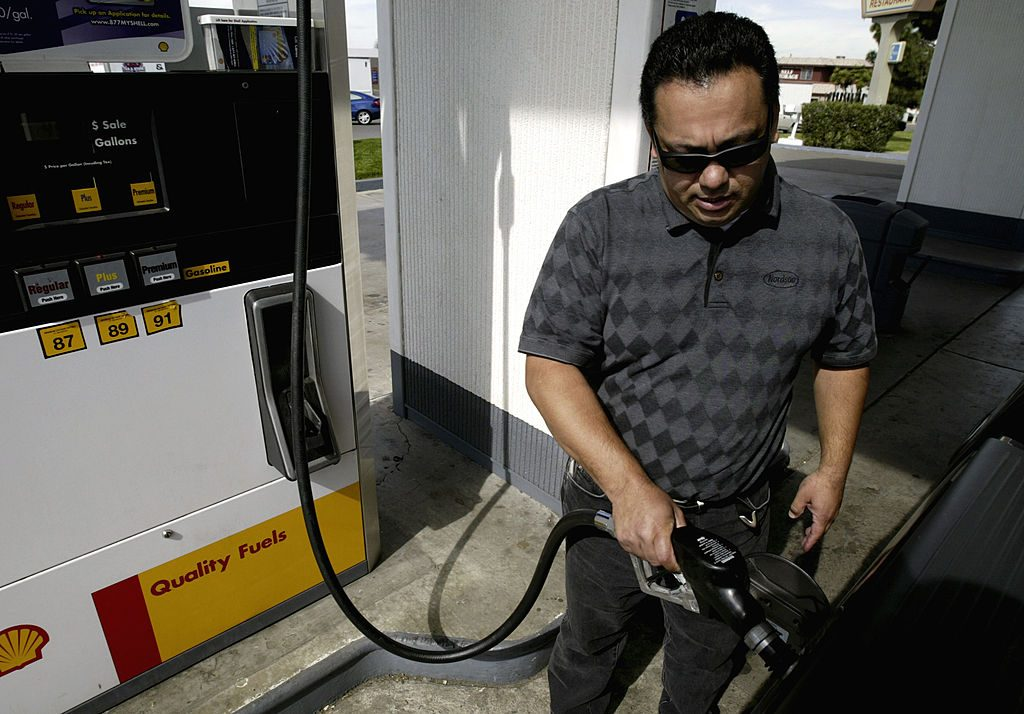 A man filing up his used pickup truck with gas.
