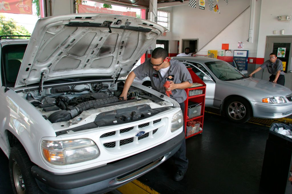 A man servicing a truck by changing the oil.