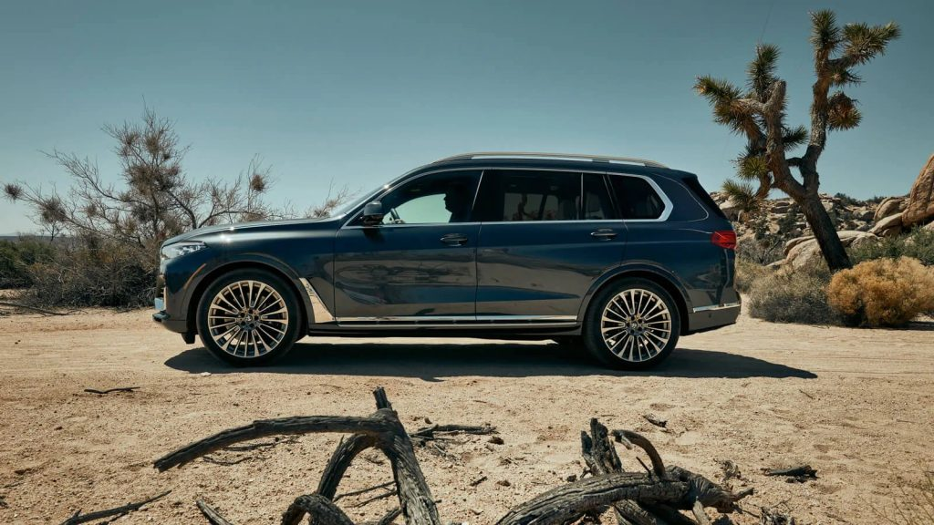 A side-view of the 2020 BMW X7 parked in the sand.