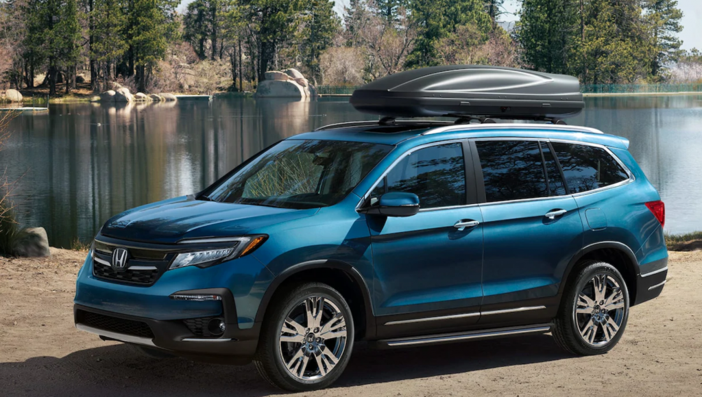 An electric blue 2020 Honda Pilot parked by a lake.