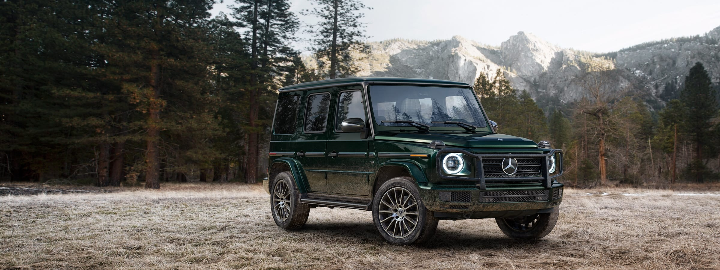 a Mercedes-Benz G-Class Wagen SUV parked in a clearing in the mountains.