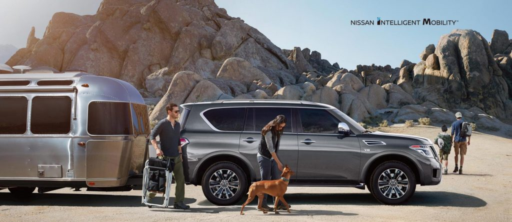 A gray 2020 Nissan Armada parked near the desert with a family and dog.