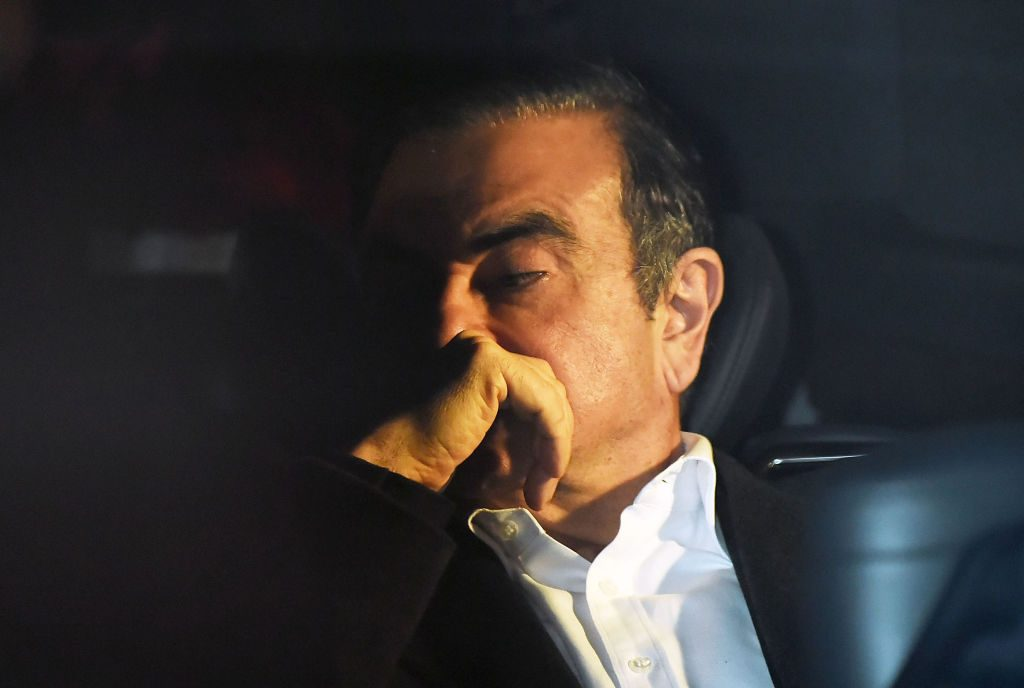 Former Renault Nissan CEO Carlos Ghosn in dark room looking down