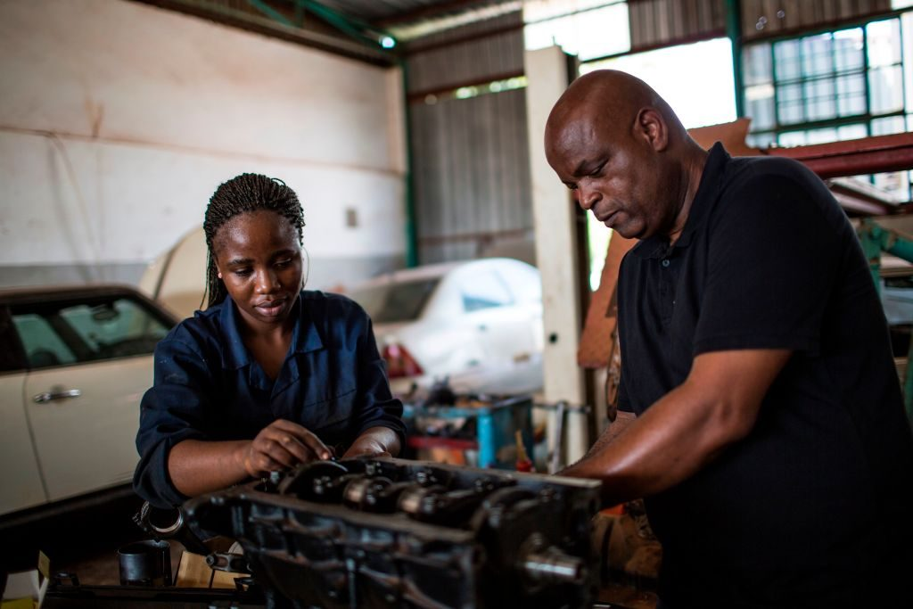 Two diesel mechanics repairing an engine
