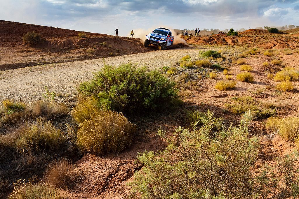 A Ford Baja Raptor racing through a desert terrain.