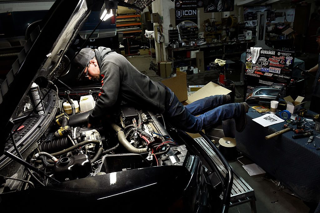A mechanic working to fix a Ford F-150 with engine problems