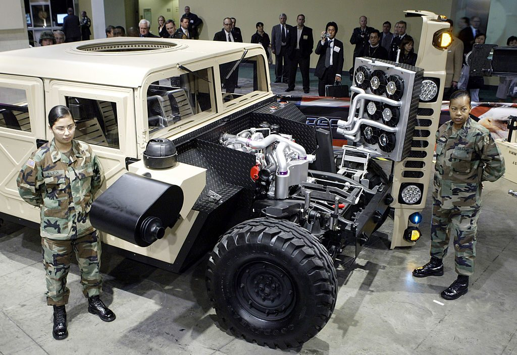 Two soldiers standing next to a military Humvee built by GM