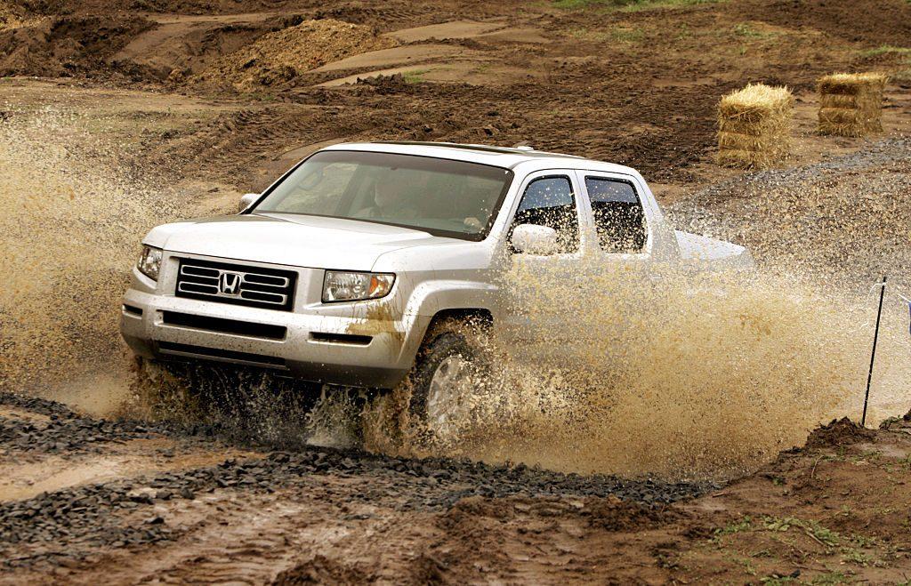 An older Honda Ridgeline driving through a puddle