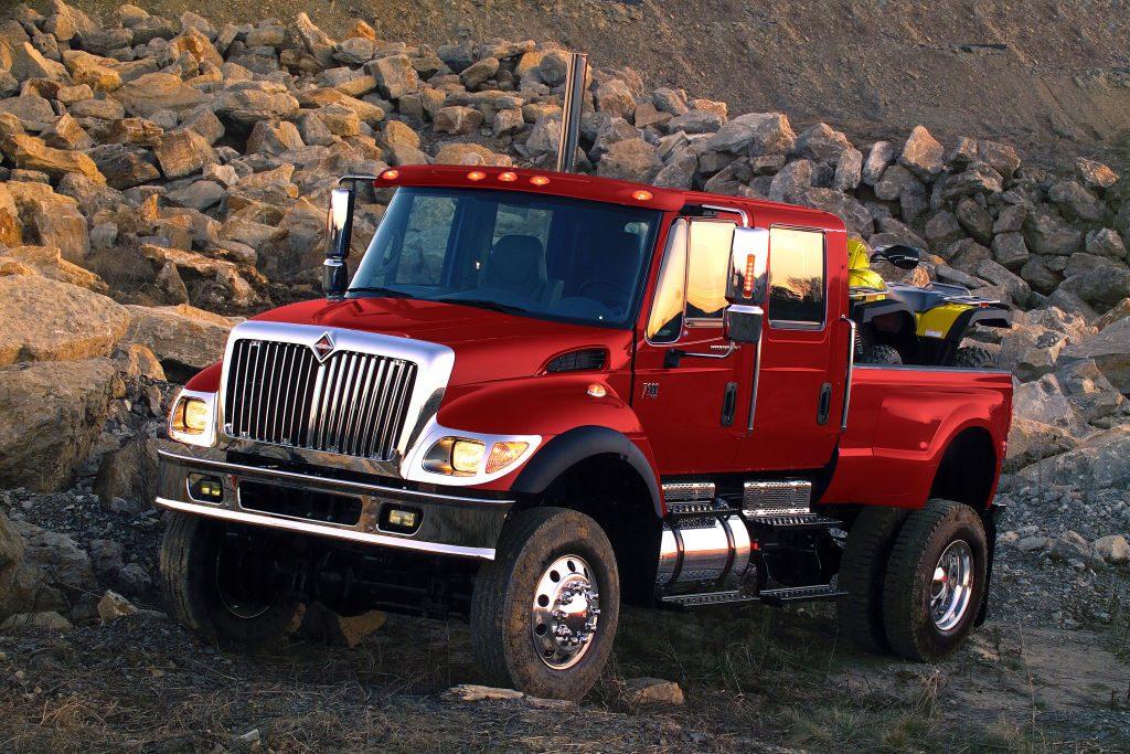 An International MXT truck driving over some rocks.