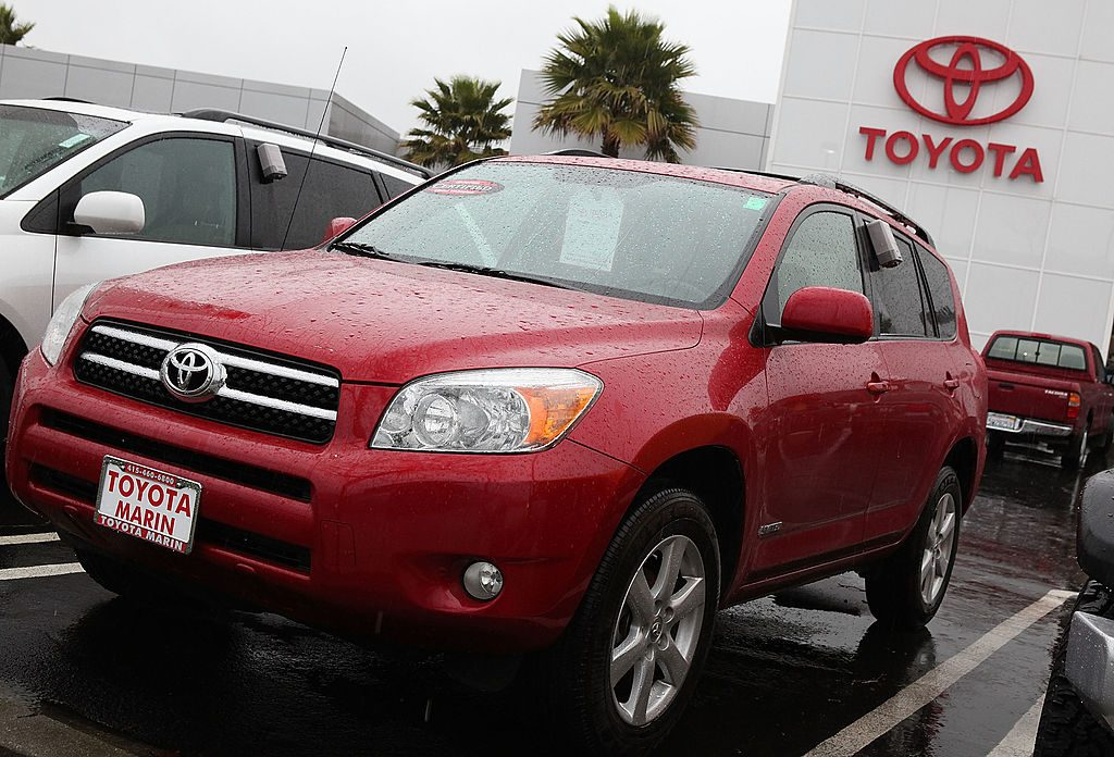 A red Toyota RAV4 on display at a car dealership.