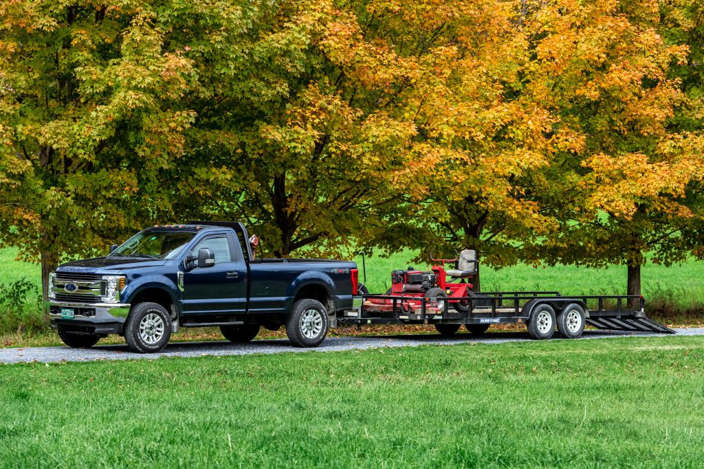 A lawn care service truck towing a lawn mower