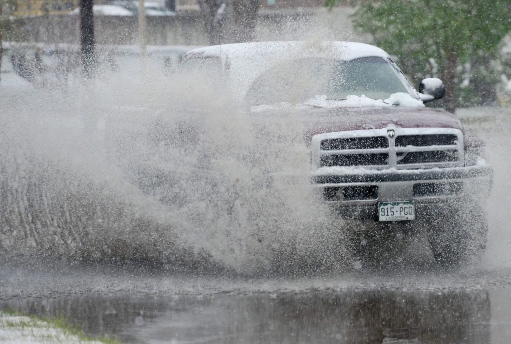 A truck splashes through a puddle off-road.