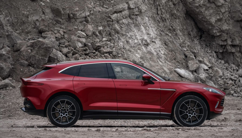 A red 2021 Aston Martin DBX SUV parked in a mountain setting.