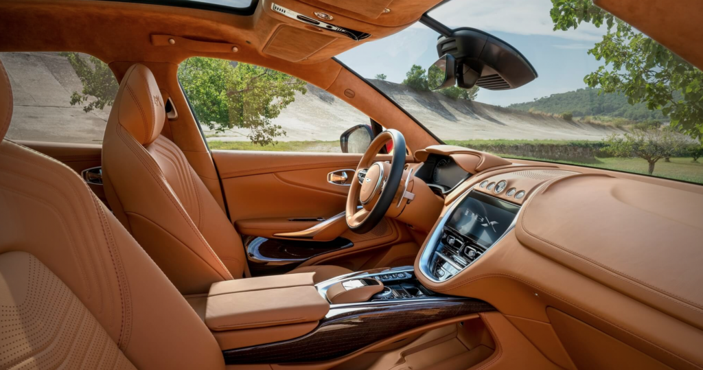 The light-brown-leather-and-wood-trim interior of the 2021 Aston Martin DBX