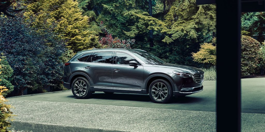 A grey 2020 Mazda CX-9 sparked in near a lush green forest.