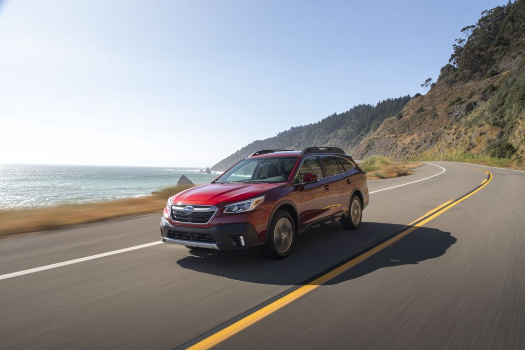 A red 2020 Subaru Outback driving on the countryside.