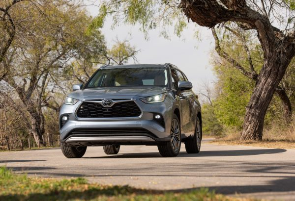 2020 Toyota Highlander three-row crossover SUV driving down the street