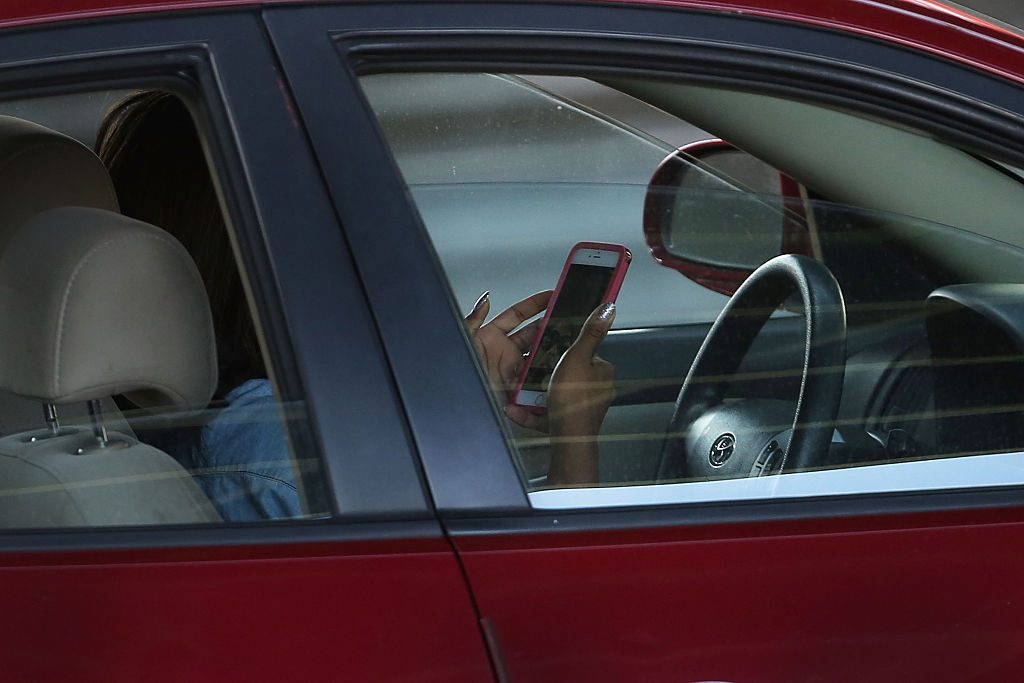 A bad driver using a phone while behind the wheel of a car