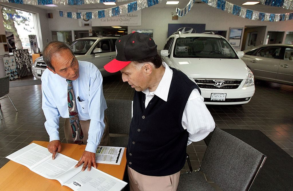 A car salesman going over the awards a car has won with a customer