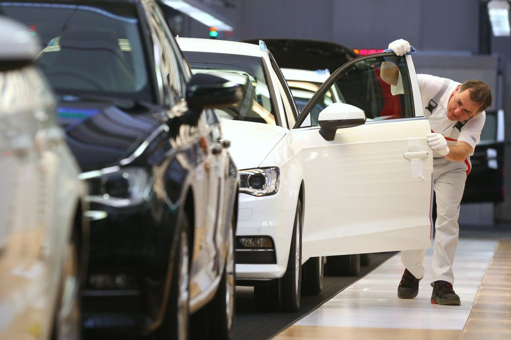 A person inspecting a car in the factory