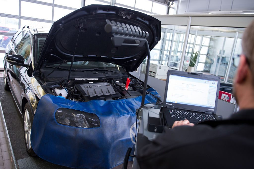 Car repair shop manager Marc Oliver Dahl has connected a VW Passat TDI to a computer used for diagnostics in the Nouvertne Volkswagen car dealership in Solingen, Germany, 04 March 2016. Photo: MARIUS BECKER/dpa | usage worldwide   (Photo by Marius Becker/picture alliance via Getty Images)