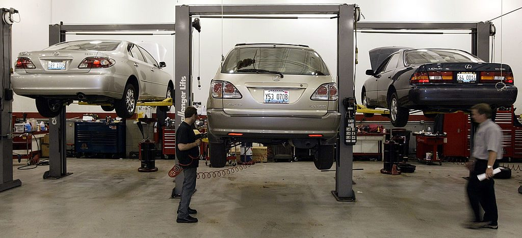 Mechanics perform maintenance on Lexus autos at a dealership.